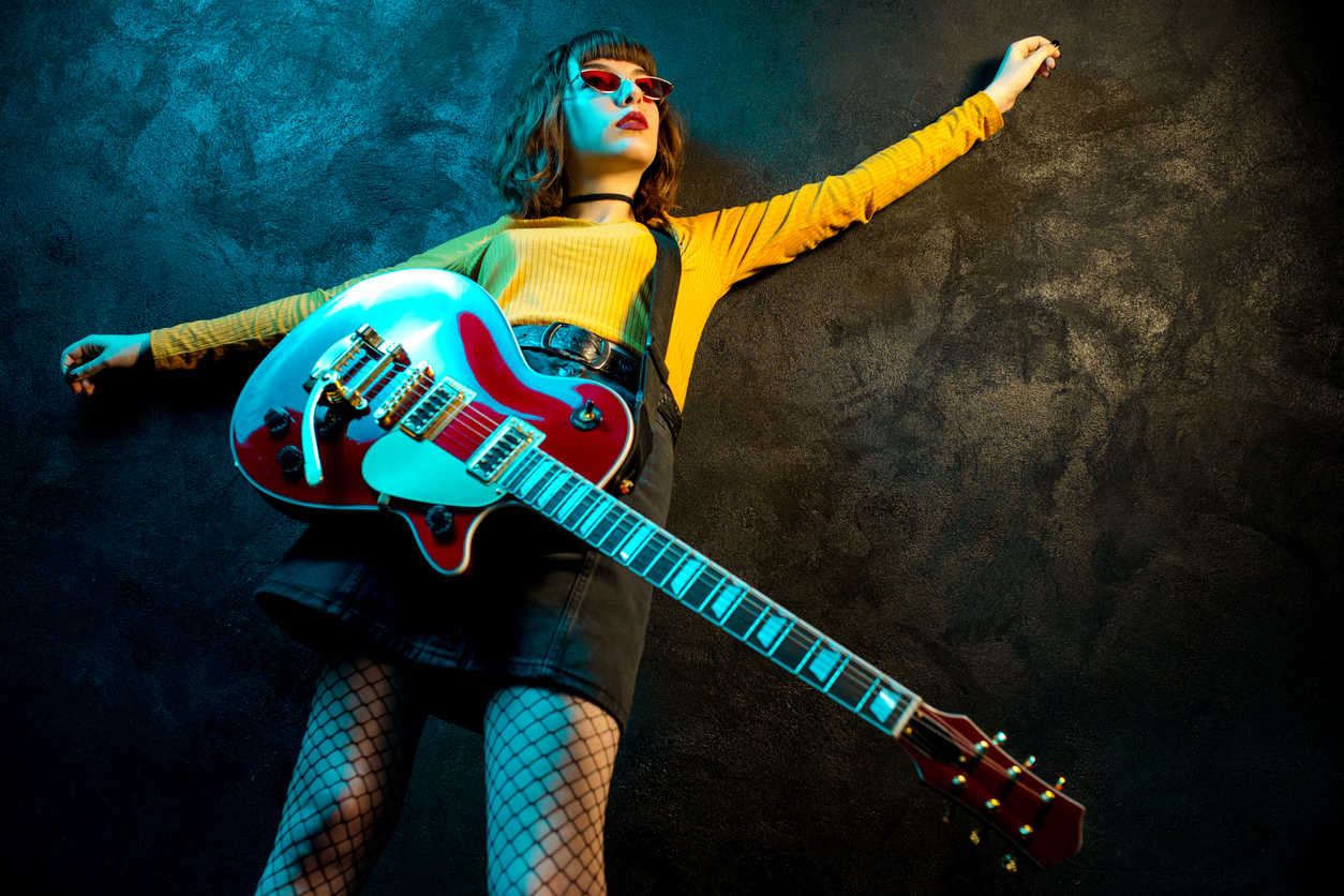 Charming hipster woman with curly hair with red guitar in neon lights. Rock musician is playing electrical guitar. 90s style concept.